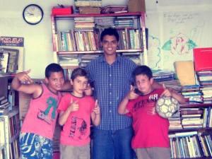 Alan e três crianças do projeto de futebol.